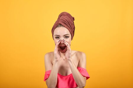 young girl with towel on her head over isolated orange background shows emotions