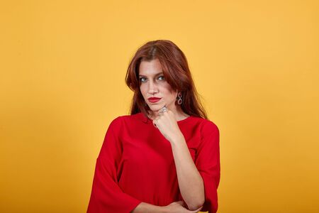 Peaceful woman propped chin on her left hand. This gesture shows that she is very serious and humorless. Charming girl stands straight at yellowish background. Brunette with gray eyes wears clips.