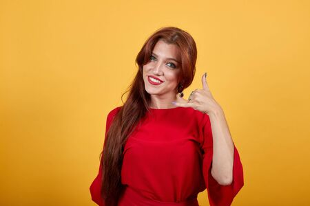 Happy girl smiling, holding left hand up and shows gesture using fingers. Pretty woman in red garnment imitates phone calling. Long-haired lady with smart eyes weares eardrops. Banco de Imagens