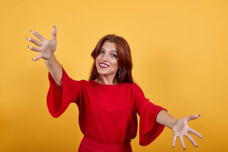 Happy girl smiling, holding hands widely opened and shows gesture of openess. Woman in delightful dress stands on orange background. Dark-haired lady with grey eyes wears eardrops. Banco de Imagens