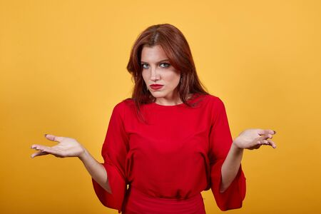 Beautiful, young girl opening her both hands looks displeased and unsatisfied. Pretty woman in contemporary clothes stands on yellow background. Lady in red has beautiful facial features.