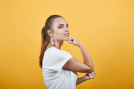 Female showing strength by turning arm around as sign of being strong also thinking is well smiling, feelings are high, dominating behavior coming up from her face