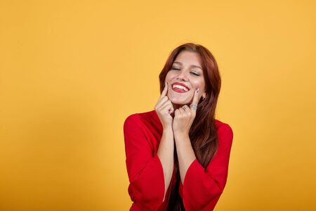 Cheerful lovely girl holding thumbs on her cheeks, smiling with widely opened mouth and closed eyes. Lovely lady standing over orange background seems very happy, pleased.