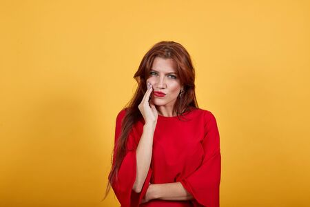 Young European woman keeping her right hand on cheek imitating a toothache. Pretty girl in red clothing with long dark hair is over isolated light background.