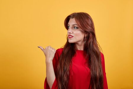 Young woman with red dress pointing to side with thumb to present a product or an idea. Charming girl looking forward on isolated light background. Banco de Imagens