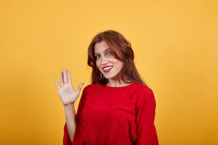 Beautiful European lady saluting with her right hand, smiling and having happy expression. Woman in red clothes over light background looks cheerful and full of energy.