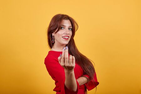 Charming woman inviting to come with hand gesture. Smiling girl in red clothing matching her lipstick looks so happy and cheerful on isolated yellow backgroud.
