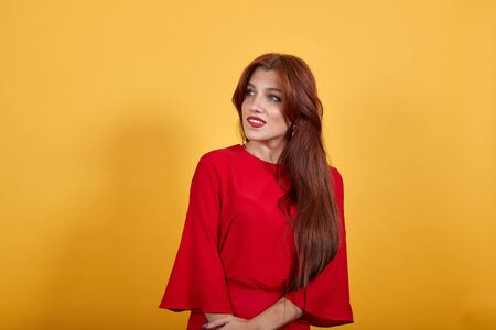 Attractive, young girl looking at right with confuse face expression. Lady in red dress stands on yellow background. Brunette has brilliant, grey eyes. Banco de Imagens
