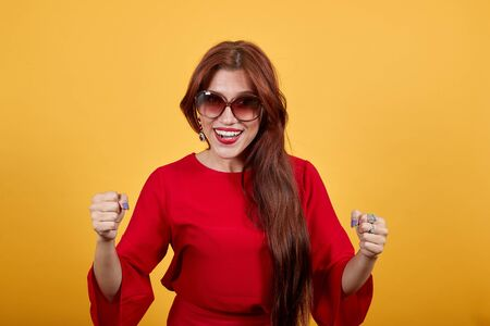 Young beautiful woman wearing brown sunglasses that matches with her pretty dress over yellow wall celebrating a victory. Lovely girl keeping hands in fists at chest level.