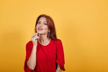 Gorgeous European woman smiling, keeping her fingers of right hand near chin. Charming woman in red garment with massive earrings standing over yellow wall.
