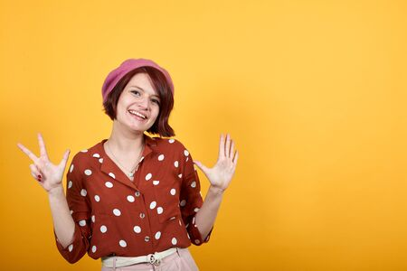 Funny caucasian young woman wearing red shirt with white polka dot over isolated background. Showing and pointing up with fingers number eight while smiling confident and happy.