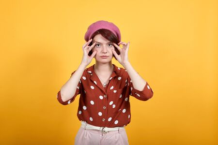 Beautiful young girl wearing red shirt in white polka dot and pretty pink hat over isolated background trying to open eyes with fingers, sleepy, tired for morning fatigue trying do not sleep