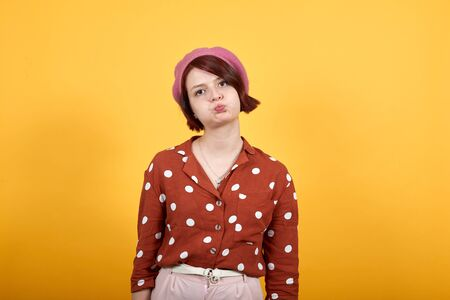 Young funny beautiful caucasian woman wearing nice pink hat and red fashion shirt puffing cheeks with funny face. Mouth inflated with air, crazy expression.