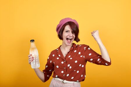 Attractive young caucasian woman having water bottle over isolated yellow background annoyed and frustrated shouting with anger, crazy and yelling with raised hand, anger concept
