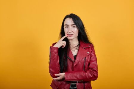 Portrait of nervous worried young woman wearing jacket looking camera, gnawing nails isolated on orange wall background in studio. People sincere emotions, lifestyle concept. Reklamní fotografie