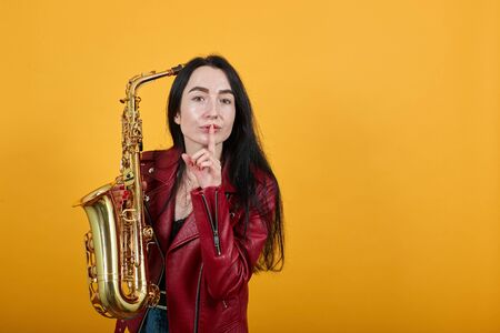 Amazed young woman in vivid casual clothes saying hush be quiet with finger on lips shhh gesture, keeping saxophone try to hear you isolated on yellow background in studio. People lifestyle concept