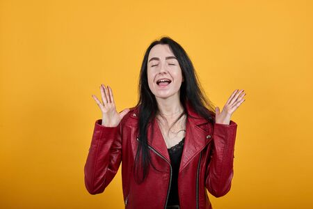 Portrait of crazy screaming young woman in vivid casual clothes keeping eyes closed, spreading hands isolated on bright orange wall background in studio. People lifestyle concept