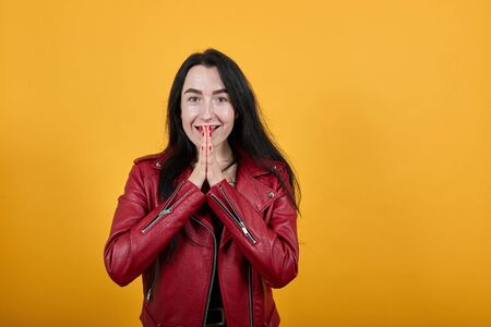 Portrait of surprised excited young woman in red jacket looking camera, covering mouth with hands isolated on yellow orange wall background in studio. People lifestyle concept Reklamní fotografie