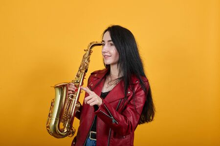 Portrait of amazed beautiful young woman in casual clothes looking, pointing index finger aside isolated on yellow orange wall background in studio, keeping saxophone. People lifestyle concept.
