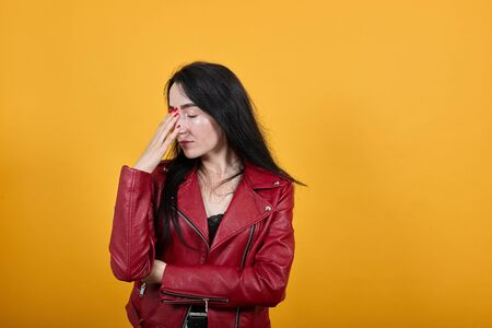 Portrait of tired exhausted young woman in vivid casual clothes keeping eyes closed, putting hand on nose isolated on bright blue background in studio. People lifestyle concept. 版權商用圖片