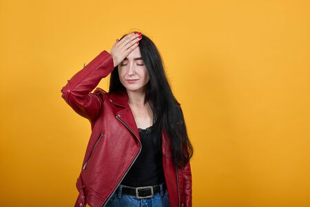 Portrait of tired young woman in vivid casual clothes keeping eyes closed, putting hand on head, face isolated on bright yellow wall background in studio. People lifestyle concept. Mock up copy space