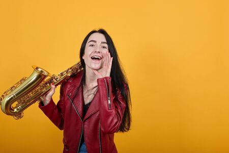 Portrait of cheerful young woman in red casual clothes looking camera screaming with hands near mouth keeps saxophone. People lifestyle concept.