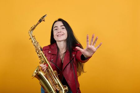Portrait of crazy young woman in red casual clothes looking camera, keeping saxophone and smiling, standing with outstretched hands isolated on orange background. People lifestyle concept 스톡 콘텐츠