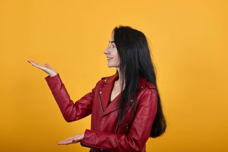 Side view of laughing young lady in casual clothes pointing hands aside, holding something isolated on orange wall background in studio. People sincere emotions, lifestyle concept.