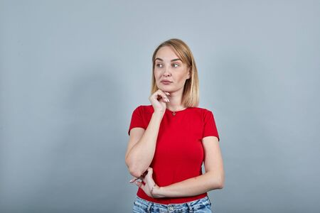 Portrait of pensive young woman in red shirt looking aside, put hand prop up on chin isolated on white wall background in studio. People sincere emotions, lifestyle concept. Reklamní fotografie