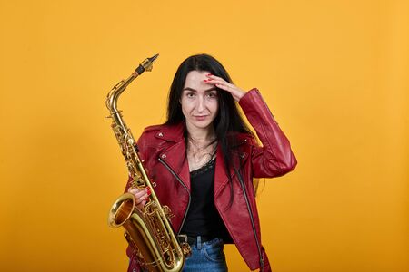 Close up brunette woman on red jacket over isolated yellow wall background, studio portrait, keeping gold saxophone