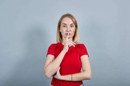 Pretty young woman in red shirt saying hush be quiet with finger on lips shhh gesture isolated on grey background in studio. People sincere emotions, lifestyle concept.