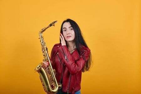 Calm young lady over isolated yellow background wearing red jacket.Keeping mouth closed and saxophone, putting hands on cheeks 스톡 콘텐츠 - 133458489