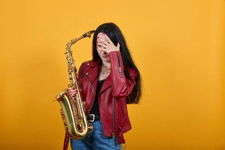 Attractive young lady in red jacket, keeping gold saxophone posing isolated on yellow wall background studio portrait. People sincere emotions lifestyle concept. Cover face with hand 스톡 콘텐츠 - 133458503