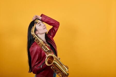 Young caucasian pretty woman over isolated yellow background has realized something and intending the solution, keeping gold saxophone