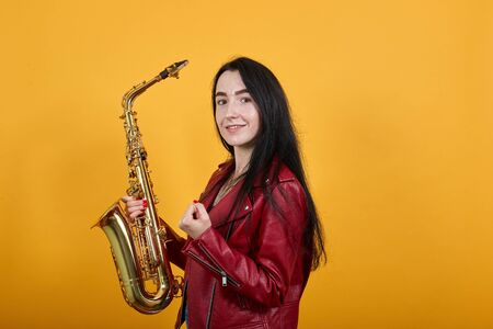 Young brunette woman in casual clothes posing isolated on orange wall background studio portrait,keeping saxophone, doing winner gesture say Yes. People sincere emotions lifestyle concept