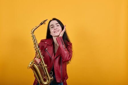 Portrait of pensive pretty young woman in red jacket looking up, putting hand on cheek isolated on yellow orange background, keeping saxophone. People sincere emotions lifestyle concept