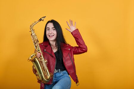 Crazy smiling young woman in casual clothes, keeping saxophone, showing palms over isolated on yellow orange wall background. People sincere emotions lifestyle concept 스톡 콘텐츠