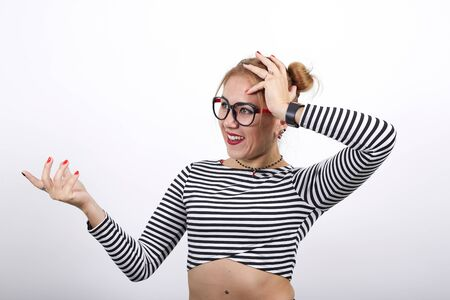 Sad tired female wearing rstriped shirt over isolated on white background in studio looking so tired like she having headache, looking on hand Reklamní fotografie