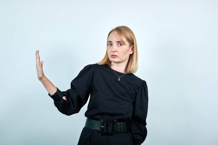 Portrait of serious young woman in dark clothes showing stop gesture with palm aside isolated on white wall background in studio. People sincere emotions, lifestyle concept.