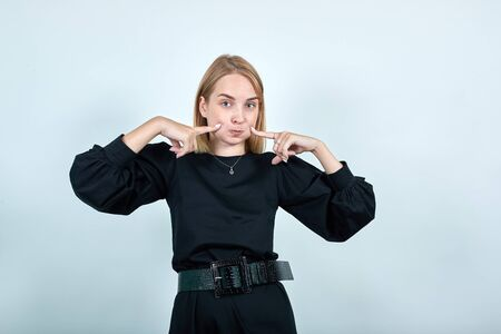 Portrait of funny young woman in black casual clothes pointing index fingers on blowing cheeks isolated on bright white orange wall background in studio. People lifestyle concept. Stok Fotoğraf