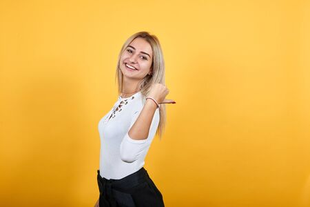 Young caucasian lady wearing pastel white shirt looking so funny, over white wall happy and pointing to the side