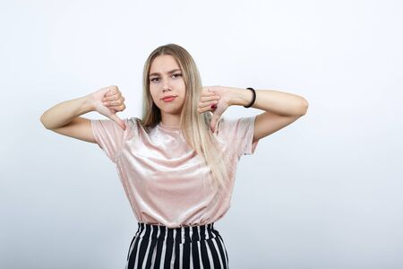Young attractive caucasian girl over isolated white background showing thumb down, looking unhappy wearing casual clothes Stock Photo