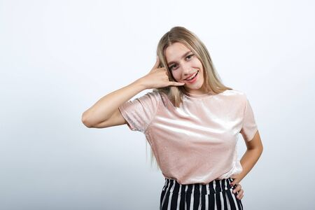 Teenager caucasian woman wearing pastel shirt over white wall making phone gesture and doubting Stok Fotoğraf