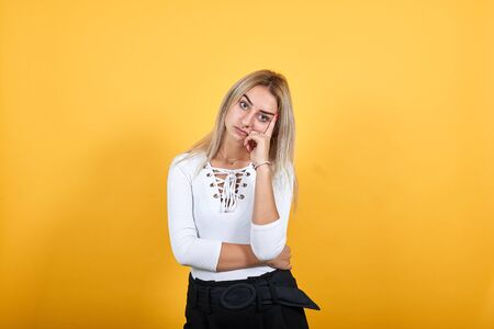 Boring young caucasian woman posing isolated on orange background in studio wearing casual shirt, keeping hand on head, headache