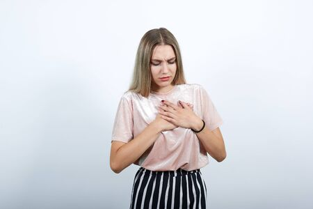 Portrait of upset pleasant young woman in casual shirt holding hands on chest, heart isolated on white background in studio. People sincere emotions, lifestyle concept. Stock Photo