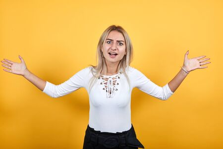 Angry cheerful young woman in casual shirt, looking camera, spreading hands isolated on orange background in studio. People sincere emotions, lifestyle concept.