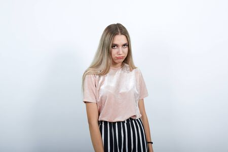 Young funny beautiful caucasian woman wearing nice pink shirt puffing cheeks with funny face. Mouth inflated with air, crazy expression. Stock Photo