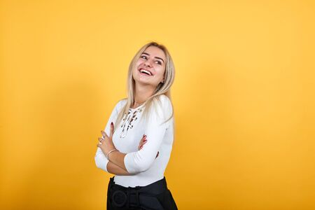 Smiling young woman in casual clothes holding hands crossed, smiling isolated on orange wall background. People sincere emotions, lifestyle concept.