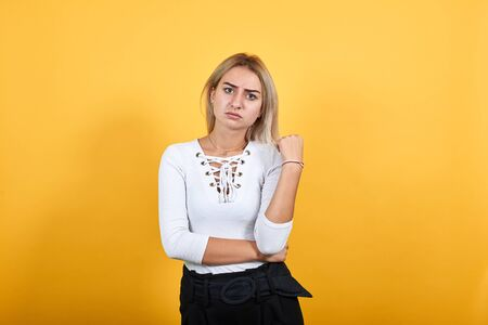 Young beautiful attractive caucasian woman keeping thumb up wearing pretty shirt on isolated orange background