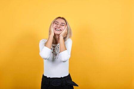 Beautiful excited blonde young woman wearing casual white shirt keeping hands on cheeks, looking so happy isolated over orange wall background, studio portrait. People lifestyle fashion concept.